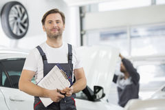 Portrait Of Confident Male Maintenance Engineer With Clipboard In Car Repair Shop Royalty Free Stock Images