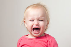Portrait Of Crying Young Baby Sit On Chair Stock Photo