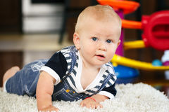 Portrait Of Cute Adorable Blond Caucasian Smiling Baby Boy With Blue Eyes Lying On Floor In Kids Children Room Royalty Free Stock Images