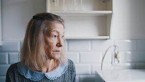 Free Portrait Of Elderly Gray Haired Lady Looking Through The Kitchen Window And Thinking. Vulnerable Lonely People During Stock Photography - 216552912