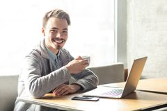 Free Portrait Of Handsome Happy Bearded Young Businessman In Grey Blazer Are Sitting In Cafe And Have A Break With Cup Of Coffee And Royalty Free Stock Photography - 152719987