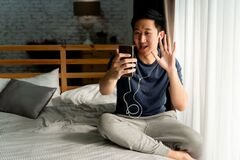 Free Portrait Of Happy 30s Aged Asian Man In Casual Clothing Making Facetime Video Calling With Smartphone At Home. He`s Royalty Free Stock Photos - 177303898