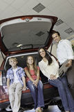 Portrait Of Happy Family Sitting At Back Of Their New Car Royalty Free Stock Images