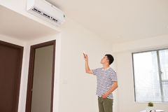 Free Portrait Of Happy Man Using Remote Control To Operate Air Condit Royalty Free Stock Image - 107304386