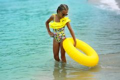 Free Portrait Of Happy Modern Child In Yellow Swimwear With Yellow Inflatable Lifebuoy On The Seashore Stock Image - 141095181