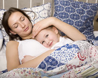 Portrait Of Happy Mother And Daughter In Bed Hugging And Smiling Stock Photos