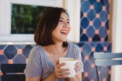 Free Portrait Of Happy Young Asian Business Woman With Mug In Hands Drinking Coffee In The Morning At Cafe. Stock Photography - 114988892