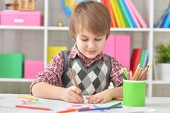 Portrait Of Little Boy Sitting At Table And Drawing With Colorful Pencils Stock Images