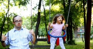 Free Portrait Of Man And Girl With Down Syndrome Swinging Stock Images - 108879294