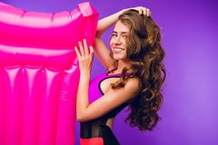 Portrait Of Pretty Girl With Long Curly Hair Smiling To Camera On Purple Background In Studio. She Wears Swimsuit And Stock Image