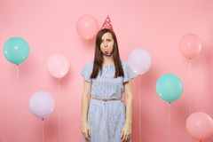 Free Portrait Of Puzzled Upset Young Woman With Party Whistle In Birthday Hat And Blue Dress On Pastel Pink Background With Royalty Free Stock Photos - 139514808