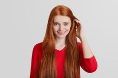 Free Portrait Of Redhead Young Female With Long Hair, Has Freckled Face, Pleasant Smile, Touches Hair, Over White Background. Royalty Free Stock Image - 107879726