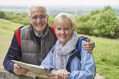 Free Portrait Of Retired Couple On Walking Holiday Resting On Gate With Map Stock Image - 160005331