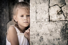 Portrait Of Sad Little Girl Standing Near Stone Wall Royalty Free Stock Image