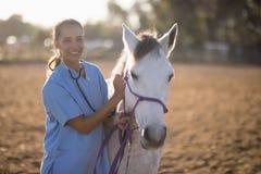 Free Portrait Of Smiling Female Vet Examining Horse Royalty Free Stock Photo - 97408035