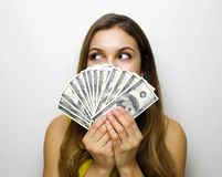 Free Portrait Of Successful Woman Covering Mouth With Fan Of 100 Dollar Bills Looking To The Side Being Satisfied About Salary Or Royalty Free Stock Photo - 140232645