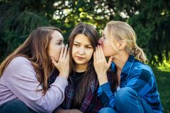 Free Portrait Of Three Young Girlfriends Who Whisper In The Park. Exchange Of News, Emotional Women Whispering Gossip Royalty Free Stock Images - 168714339