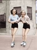 Portrait Of Two Young Women With Roller Blades Skating On The Road And Smiling Royalty Free Stock Image
