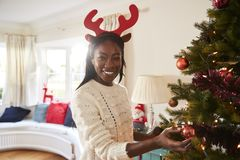 Free Portrait Of Woman Wearing Antlers Hanging Decorations On Christmas Tree At Home Royalty Free Stock Photography - 136295047