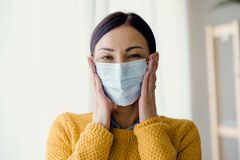 Free Portrait Of Young Asian Woman,  Putting On A Medical Surgical Disposabhttpsle Face Mask To Prevent Infection Stock Photos - 174590283