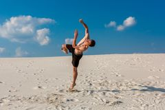 Free Portrait Of Young Parkour Man Doing Flip Or Somersault On The Sand. Stock Image - 99683641