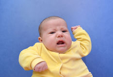 Portrait of the offended baby on a blue background Royalty Free Stock Photo