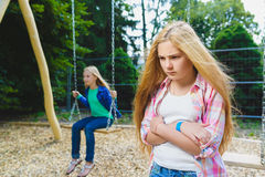 Portrait of offense child at park. On the background other girl riding a swing Royalty Free Stock Photos