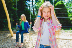 Portrait of offense child at park. On the background other girl riding a swing Stock Photography