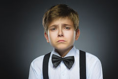 Portrait of offense crying boy  on gray background. Negative human emotion, facial expression. Closeup Stock Image