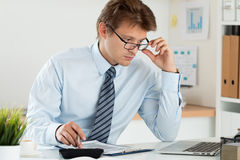 Portrait of office worker adjusting his glasses. Portrait of bookkeeper or financial inspector adjusting his glasses making report, calculating or checking royalty free stock photo