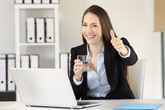 Office worker holding a glass of water looking at you Royalty Free Stock Photos