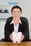 Portrait of an office worker holding a piggybank. In her office Stock Photo