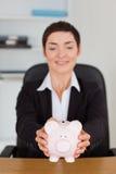 Portrait of an office worker holding a piggybank Stock Photo