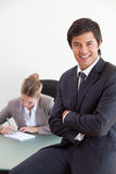 Portrait of an office worker posing while his colleague is working Stock Photos