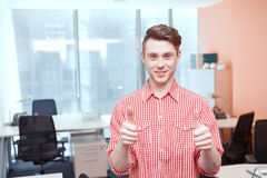 Portrait of office worker shoving thumbs-up Stock Images