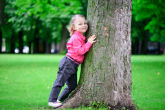 Portrait oflittle girl embracing tree in park Stock Images