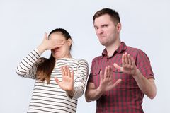 Portrait ofyoung couple looking on something unpleasant gesturing with hands refusing to buy it. Or to look stock photo