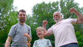 Portrait og happy family - grandpa, father and his son smiling and showing their muscles outdoor in park on background