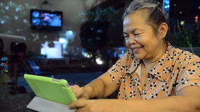 Portrait of old asian people, happy senior asia womam. Looking at tablet and smiling stock video footage