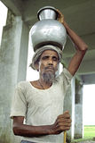 Portrait old Bangladeshi man lugging water jug Stock Photography