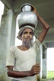 Portrait old Bangladeshi man lugging water jug Stock Photography