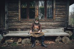 Old bearded forester with axe near wooden hut. Portrait of old bearded forester with axe near wooden hut stock photos