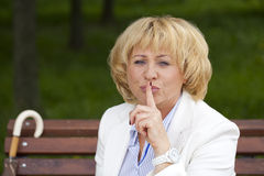 Portrait of old blonde woman with finger on lips Stock Photos