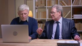 Portrait of old businessmen sitting together at the table working with laptop and discussing actively the contract. Portrait of old businessmen sitting together stock video footage