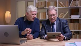 Portrait of old businessmen working together with laptop and tablet discussing seriously the project. Portrait of old businessmen working together with laptop stock footage