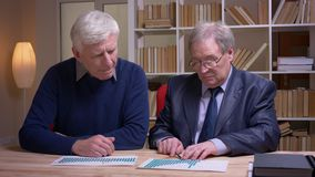 Portrait of old businessmen working together with statistic documents discussing actively the future common project. Portrait of old businessmen working stock footage