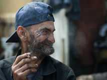 Portrait. Old dirty homeless man smoking a cigarette and smiling Royalty Free Stock Photo