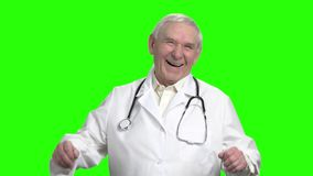 Portrait of old doctor laughing, slow motion. Senior doctor heartily laughing out loud and holding stomach, slow motion stock video