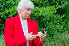 Portrait of old grandmother use technology outdoors at sun day. modern caucasian granny finger touch the touchscreen her. Phone. she has smartphone in her adult stock photography