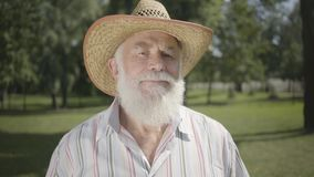 Portrait old grey-haired bearded man in straw hat looking at camera smiling standing in the park. Leisure outdoors. Confident old man with long white beard in stock video footage